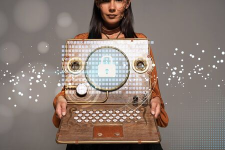 cropped view of steampunk woman in top hat with goggles showing vintage laptop with internet security illustration isolated on grey