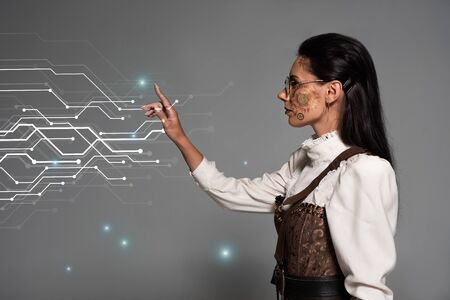 cropped view of steampunk young woman in white blouse pointing with finger at glowing cyber illustration on grey