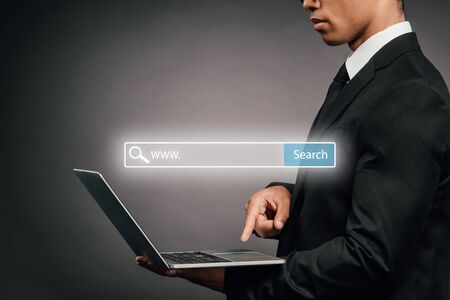partial view of african american businessman using laptop on dark background with search bar illustration