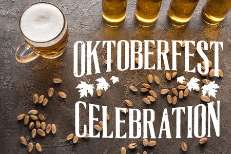 top view of bottles and glass of light beer near scattered pistachios on grey surface with Oktoberfest celebration lettering