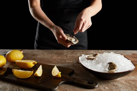 cropped view of woman holding fork near oyster isolated on black