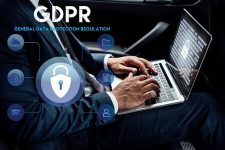 partial view of african american businessman using laptop with gdpr illustration in car