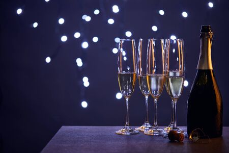 champagne in bottle and glasses with blue christmas lights bokeh Standard-Bild - 134912118