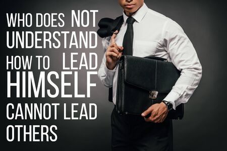 cropped view of african american businessman with leather briefcase and who does not understand how to lead himself cannot lead others lettering