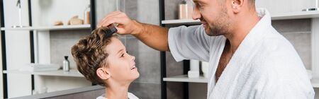 panoramic shot of handsome father brushing hair of cute son in bathroom