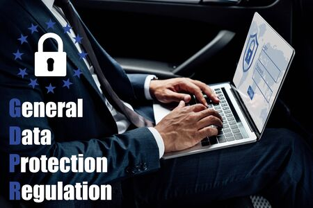 partial view of african american businessman using laptop in car with gbpr illustration Stock Photo