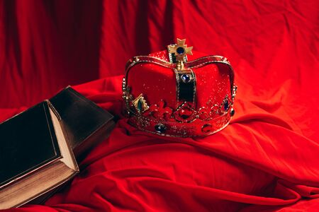 ancient golden crown with gemstones on red cloth with books