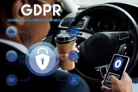 back view of african american businessman using smartphone with gdpr illustration and drinking coffee in car