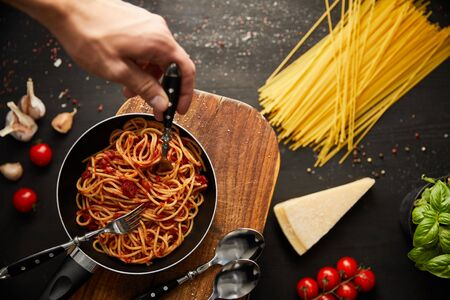 cropped view of man putting fork in tasty bolognese pasta in frying pan on black background