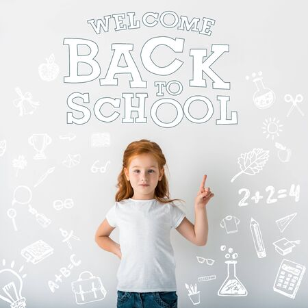 cute redhead kid looking at camera and pointing with finger near welcome back to school letters on white 스톡 콘텐츠