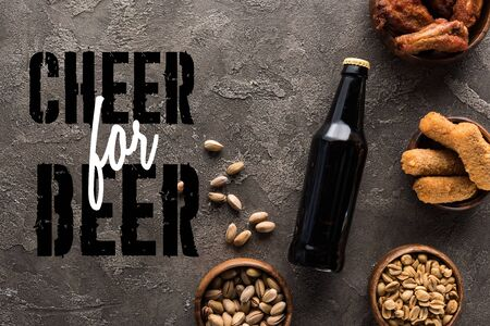top view of bottle of dark beer near bowls with snacks on grey surface with cheer for beer lettering Stok Fotoğraf