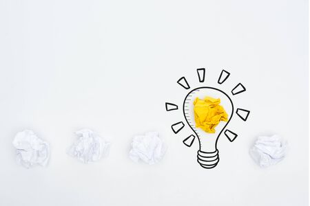 top view of white and yellow crumpled paper balls and illustration of light bulb on white background, business concept