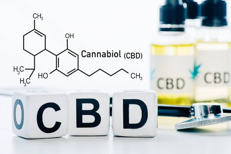selective focus of cubes with cbd lettering near oil and stethoscope isolated on white with cbd molecule illustration