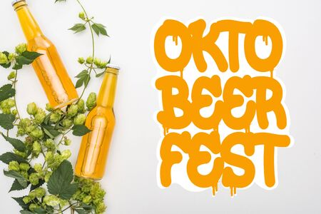 top view of beer in bottles with green hop on white background with orange Oktoberfest lettering