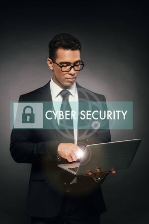 african american businessman using laptop on dark background with cyber security illustration Stock Photo