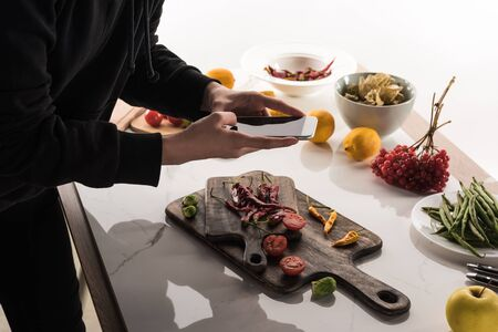 cropped view of female photographer making food composition for commercial photography on smartphone Stock Photo