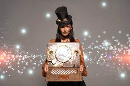 steampunk woman in top hat with goggles showing vintage laptop with glowing digital illustration isolated on grey