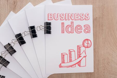 top view of white paper sheets arranged with binder clips, business idea inscription and infographics illustration on wooden table, business concept