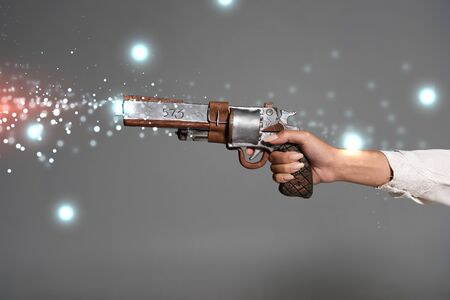 cropped view of woman holding vintage revolver isolated on grey