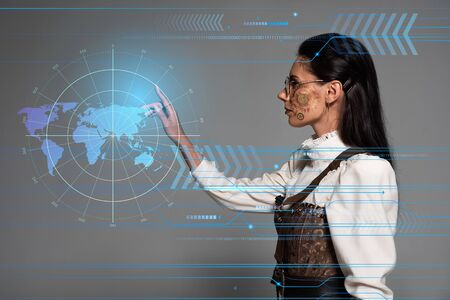 cropped view of steampunk young woman in white blouse pointing with finger at digital map on grey