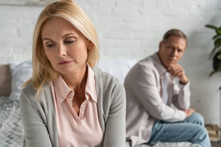 Selective focus of worried woman with husband sitting on bed