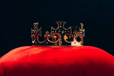 antique golden crown with gemstones on red pillow, isolated on black Imagens
