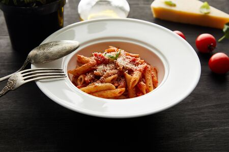 selective focus of tasty bolognese pasta with tomato sauce and Parmesan in white plate near ingredients and cutlery on black wooden background Фото со стока