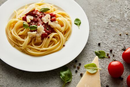 tasty bolognese pasta with tomato sauce and Parmesan on white plate near ingredients on grey background Фото со стока