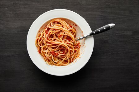 top view of tasty bolognese pasta with tomato sauce in white plate on black wooden background