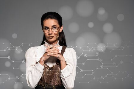 dreamy steampunk woman looking away with clenched hands near data illustration isolated on grey