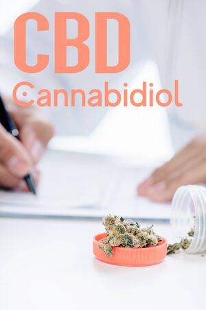 selective focus of container with medical cannabis near doctor writing prescription and with cbd illustration