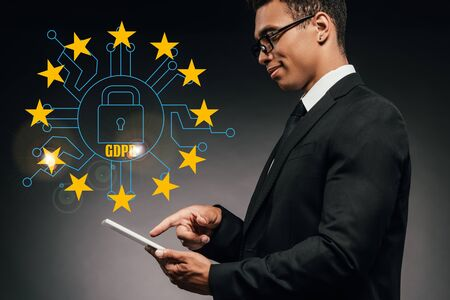 side view of smiling african american businessman using digital tablet on dark background with gdpr illustration