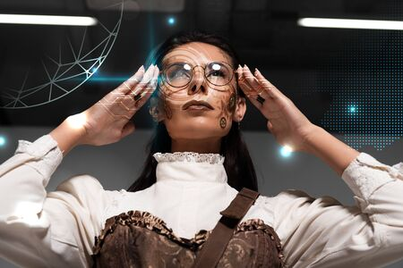 low angle view of steampunk woman with makeup touching glasses