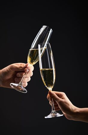 cropped view of couple clinking with champagne glasses and celebrating christmas eve, isolated on black