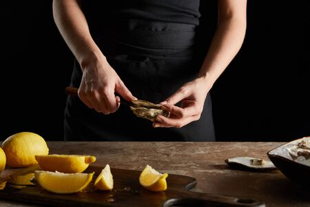 cropped view of woman holding knife while opening oyster near lemons on cutting board isolated on black