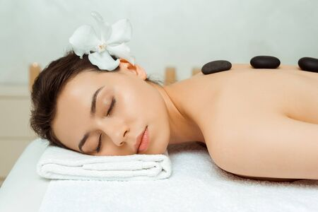 attractive woman with hot stones on back lying on massage table in spa