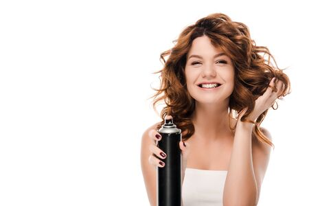 happy curly woman holding hair spray bottle isolated on white