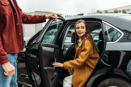 Taxi driver opening car door for smiling woman