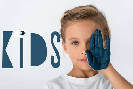 kid with blue paint on hand covering face near kids letters on white