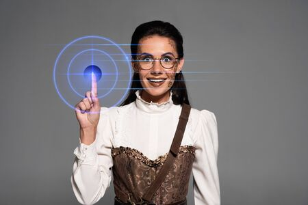 front view of excited attractive steampunk woman showing idea sign isolated on grey Stock fotó