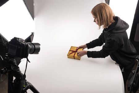beautiful photographer taking photos of christmas gift on digital camera on white in photo studio Stock Photo