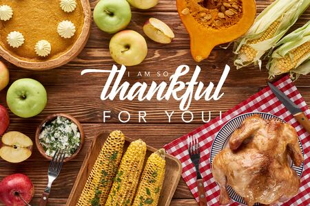 top view of pumpkin pie, turkey and vegetables served at wooden table with i am so thankful for you illustration Banco de Imagens