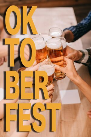 cropped view of multicultural friends clinking glasses with beer in pub with Oktoberfest illustration Stock Illustration - 134915678