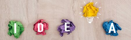 panoramic shot of multicolored crumpled paper balls, idea word and light bulb illustration on wooden surface, business concept