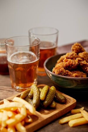 selective focus of delicious chicken nuggets, french fries and gherkins near glasses of beer on wooden table isolated on grey Stock Photo