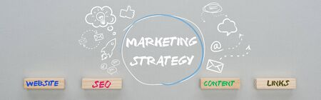 panoramic shot of marketing strategy inscription near multimedia icons illustration and wooden blocks with website, seo, content, links words on grey background,  business concept