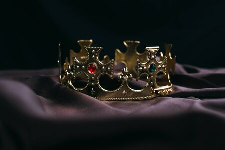 retro golden crown with gemstones on black cloth