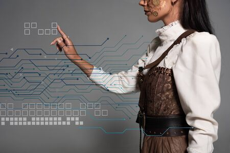 cropped view of steampunk young woman pointing with finger at data illustration