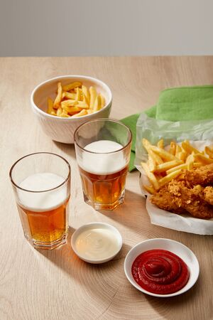 glasses of beer, chicken nuggets with french fries, ketchup and mayonnaise on wooden table on grey background Stock Photo