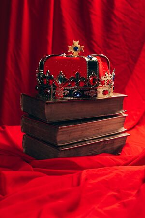 ancient golden crown with gemstones on books on red cloth Фото со стока - 134916071
